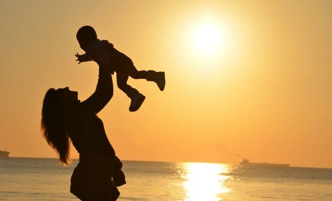 https://www.pexels.com/photo/woman-carrying-baby-at-beach-during-sunset-51953/