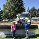 children standing in front of a bulldozer in summer